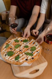 Male and female hands take pizza from the table. there is wine on the table. valentine's day date