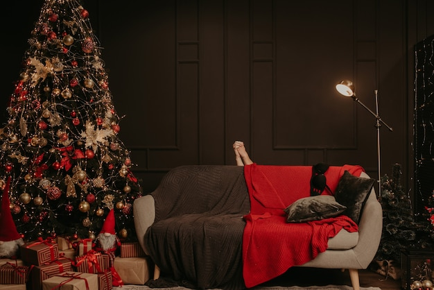 Male and female holding hands, bare intertwined, hid behind couch sofa. decorated house for new year.