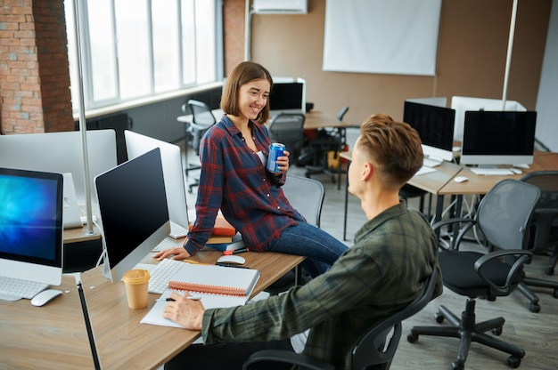 Male and female it specialists talks in office. web programmer or designer at workplace, creative occupation. modern information technology, corporate team