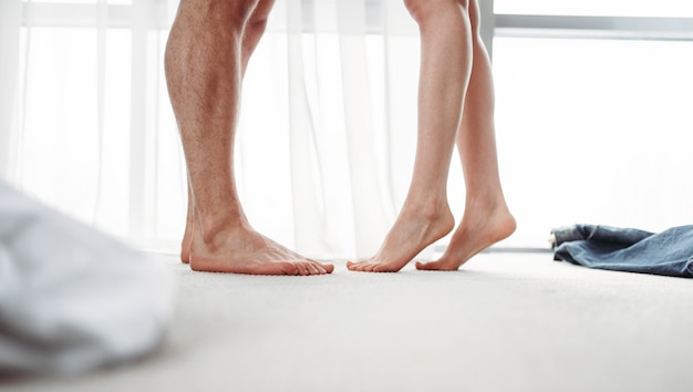 Male and female legs, intimate games in bedroom. couple intimacy, intimate desire of passionate partners