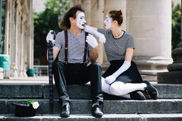 Male and female mime artist sitting on staircase