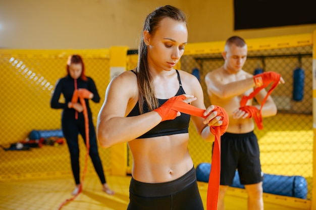 Male and female mma fighters wraps bandages on hands in gym.