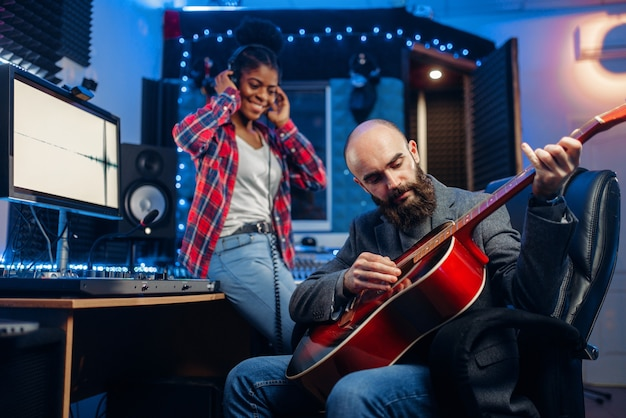 Male and female musicians in headphones and with guitar in audio recording studio.