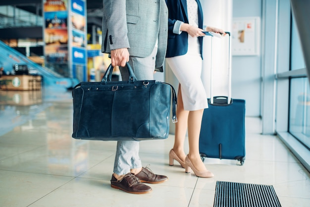 Male and female passengers with luggage in airport, business trip. businessman and businesswoman in air terminal