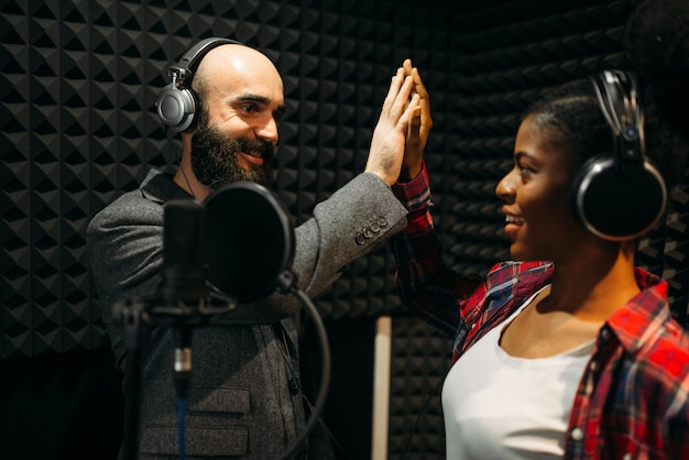 Male and female performers in headphones songs in audio recording studio. musicians on record, professional music mixing
