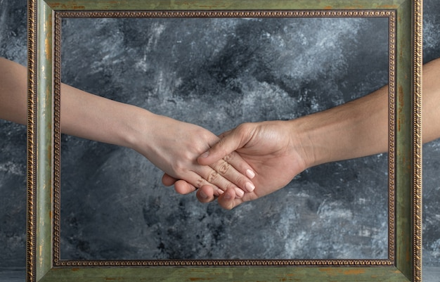 Male and female shaking hands in middle of picture frame.