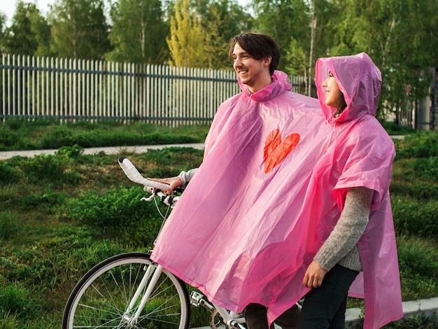 Un maschio e una femmina in un impermeabile di plastica rosa condiviso che camminano con una bicicletta per un appuntamento