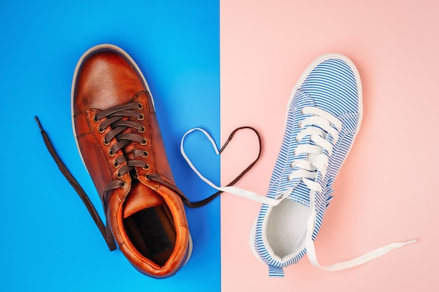 Male and female shoes on blue and pink background with shoelaces in a shape of heart