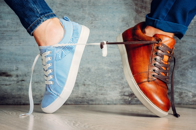 Male and female shoes go in different directions and tied with laces.