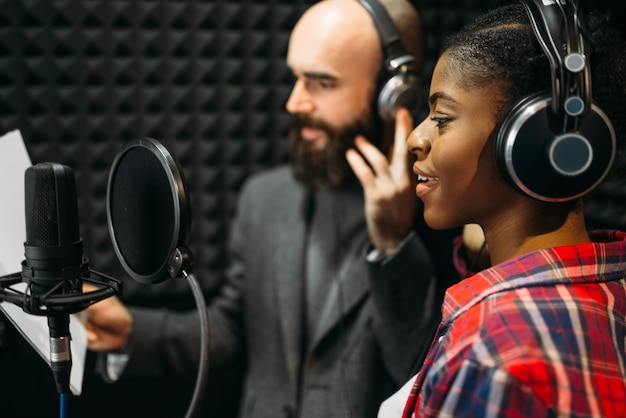 Male and female singers in audio recording studio
