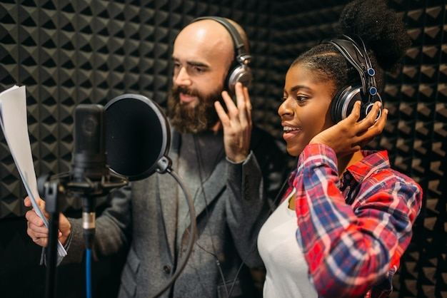 Male and female singers in headphones songs in audio recording studio.