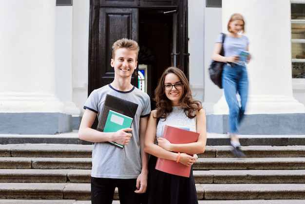 Male and female students standing on stairs of college