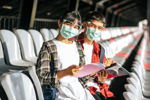 Male and female students wear masks and sit and read on the field chair