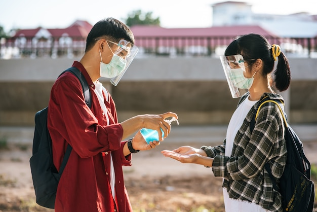 Studentesse e uomini indossano maschere e stringono il gel per lavarsi le mani.