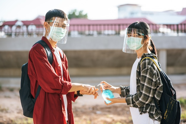 Male and female students wear masks and squeeze the gel to wash their hands.