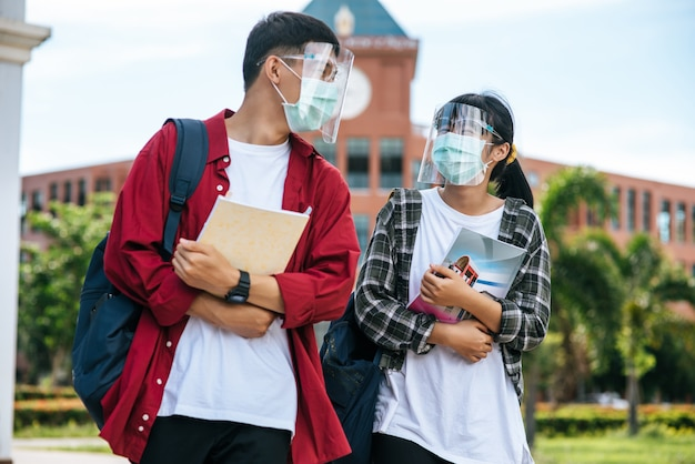 Male and female students wear masks and stand in front of the university.