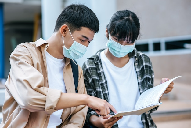 Studentesse e uomini che indossano maschere siedono e leggono libri sulle scale