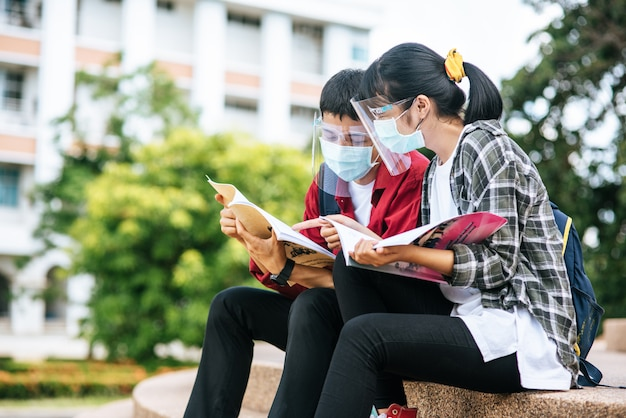 Male and female students wearing masks sit and read books on the stairs