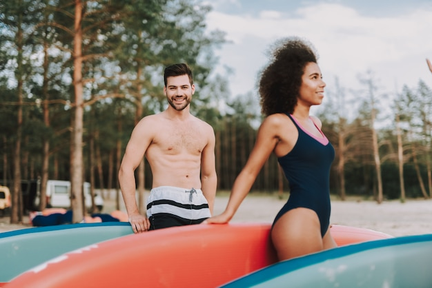 Male and female surfers go on beach.