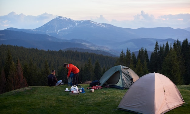 Male and female tourists in the camping near two tents while hiking together with their backpacks.