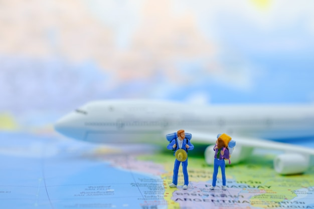 Male and female traveler miniature figures with backpack standing on world map with airplane model.