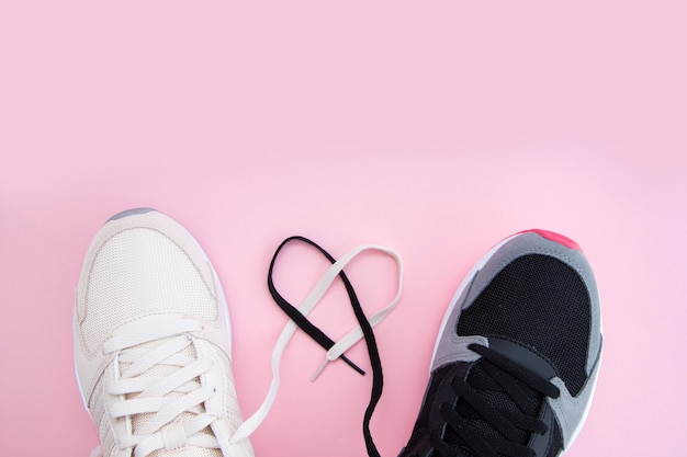 Male and female white and black sneakers and laces in the form of a heart on a pink background