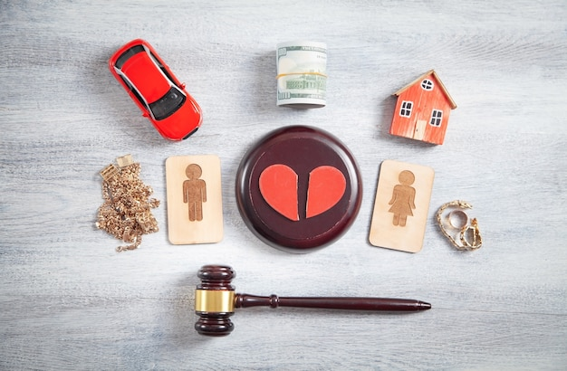 Male and female wooden symbols, gavel, house, car, broken heart and judge gavel.