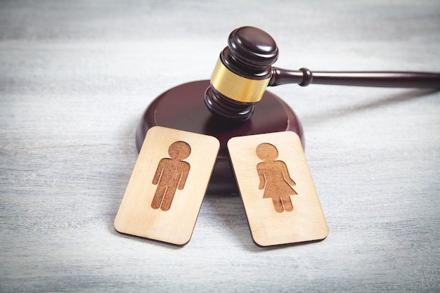 Male and female wooden symbols and judge gavel