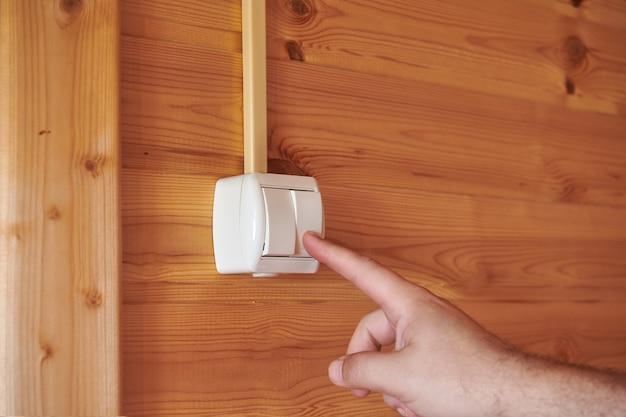 나무 벽에 장착된 전등 스위치를 켜는 남성 손가락. 집의 전기 장비. 복사 공간이 있는 보기를 닫습니다.