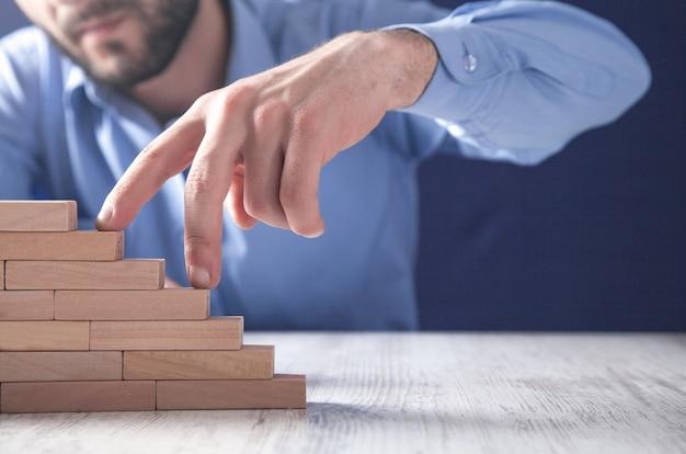 木製のブロックの階段を登る男性の指。