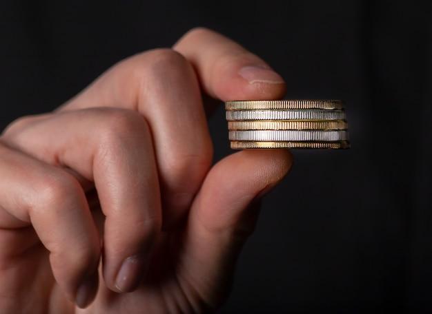동전 더미를 들고 남성 손가락입니다. 돈 세탁, 검은 거짓 회계의 개념.