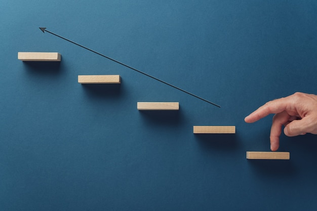Male fingers walking along the upward pointing arrow by the staircase of wooden pegs in a conceptual image of business growth. over navy blue background.