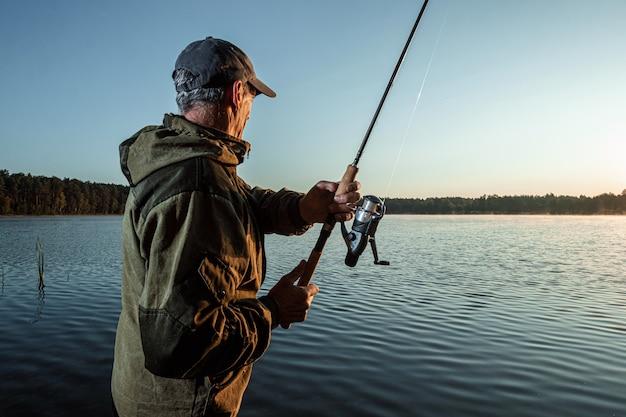 Мужской рыбак на рассвете на озере ловит удочку рыбалка хобби отпуск
