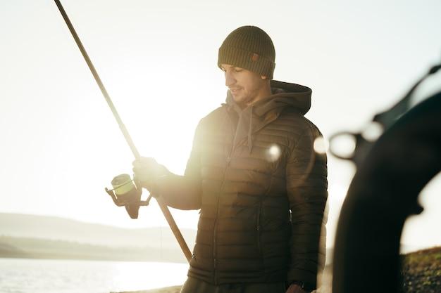 日の出の湖で釣りをする男性の漁師