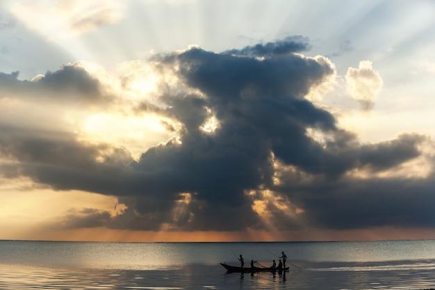 Рыбак-мужчина плывет на деревянной лодке в океане деревянная лодка на волнах океана рыбак Premium Фотографии