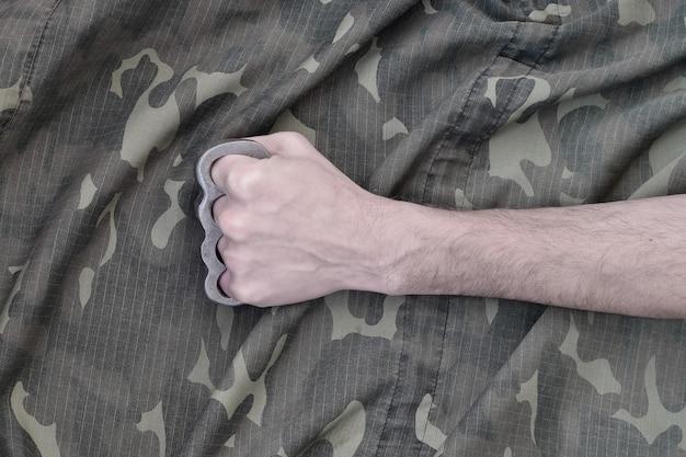 カモフラージュジャケットの壁にブラスナックルを持った男性の拳。スキンヘッドカルチャーのコンセプト、手作りの近接武器