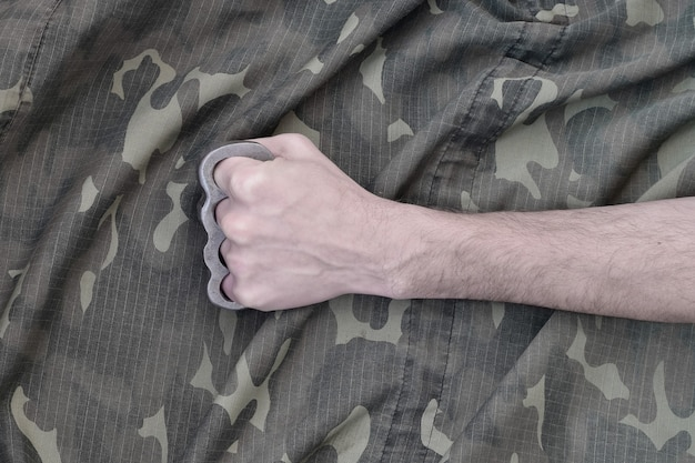 Male fist with brass knuckles on the wall of a camouflage jacket. the concept of skinhead culture, handmade melee weapons