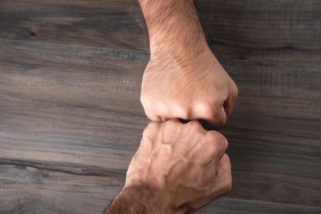男性の拳は木製の背景に優しいタッチ