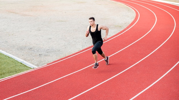 Male fitness athletic man running on the track field