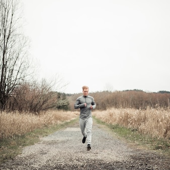 Male fitness young man running on dirt road over the field
