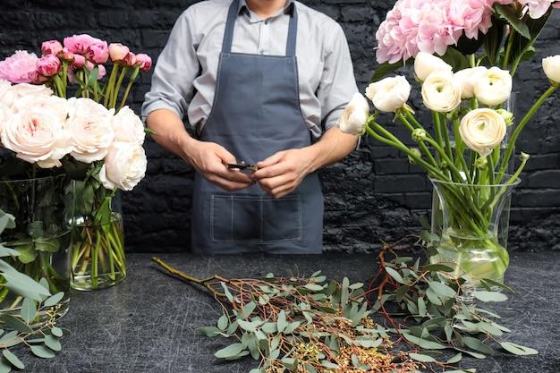 Мужской флорист создает красивый букет в цветочном магазине, крупным планом