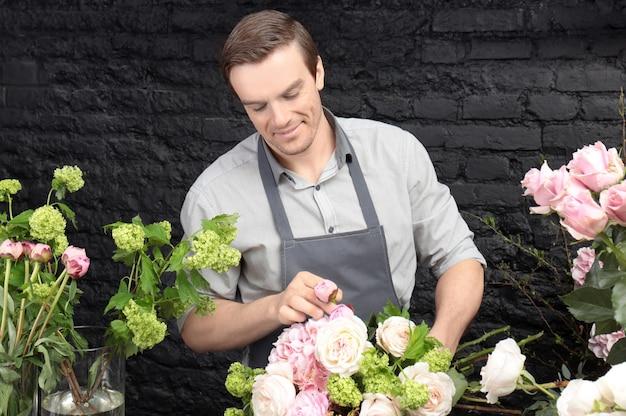 フラワーショップで美しい花束を作成する男性の花屋