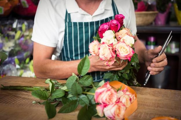 バラとshearの束を保持している男性の花屋