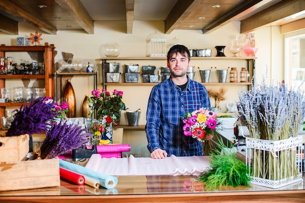 Male florist making bouquet in flower shop