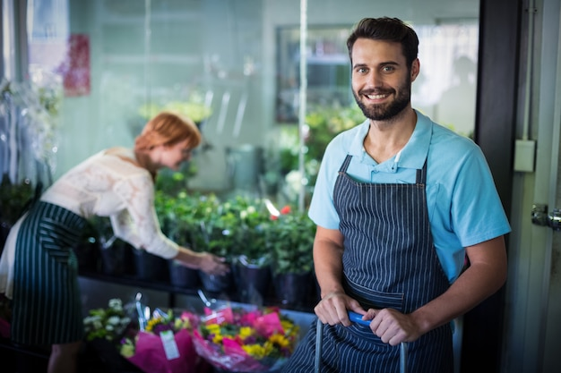 Male florist standing while female florist working in the background