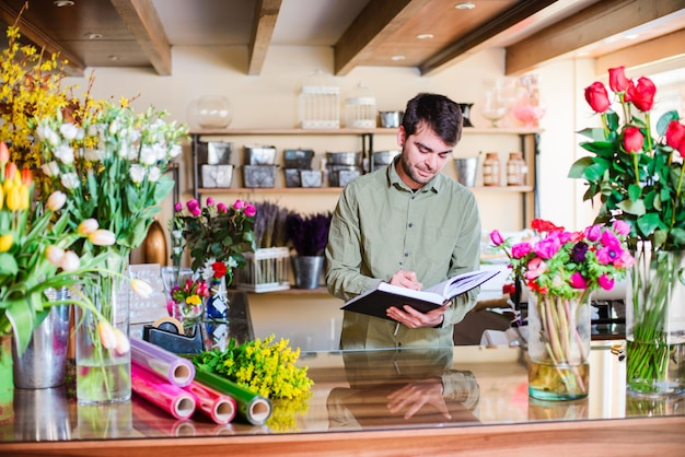Male florist taking notes in a flower shop