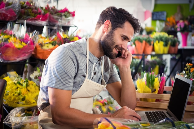 Мужской флорист разговаривает по мобильному телефону во время использования ноутбука