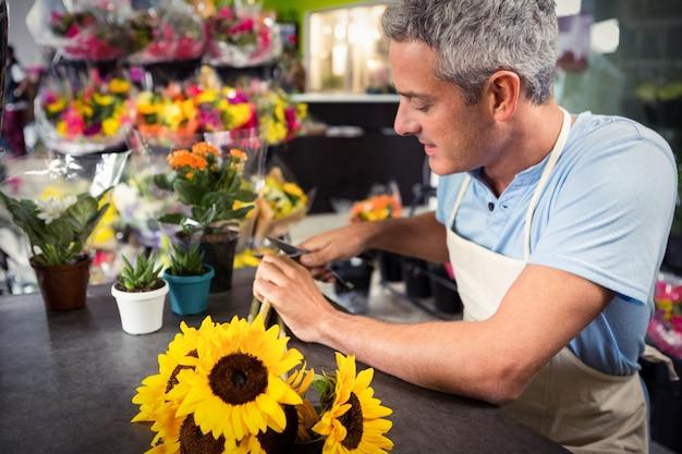 男性の花屋フラワーショップで花の茎をトリミング