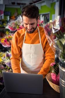 Male florist working on laptop