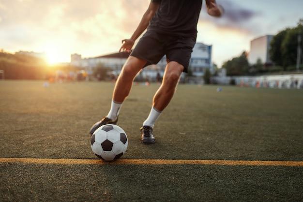 남자 축구 선수는 필드에 공을 안타. 야외 경기장의 축구 선수, 경기 전 운동, 축구 훈련